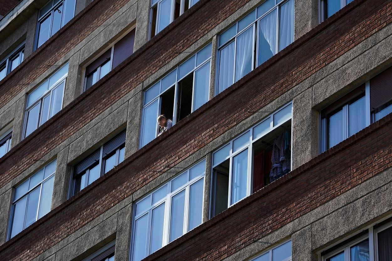 Una mujer mira desde una de las ventanas de su vivienda en Bilbao. REUTERS/Vincent West