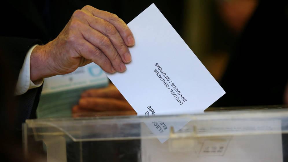 Una persona deposita su papeleta en una urna. REUTERS
