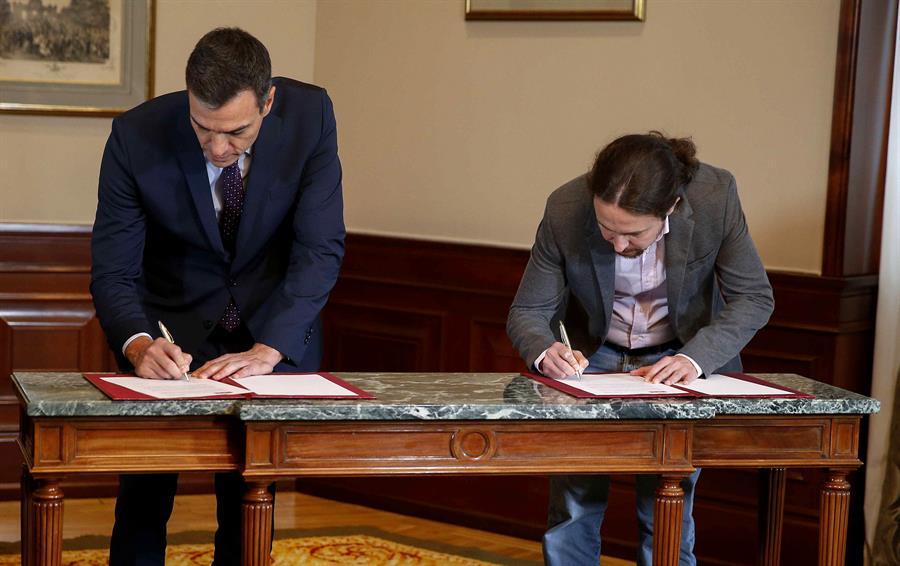El presidente del Gobierno español en funciones, el socialista Pedro Sánchez, y el líder de Podemos, Pablo Iglesias, durante la firma en el Congreso de los Diputados de un acuerdo para la formación de un Ejecutivo de coalición. EFE/Paco Campos