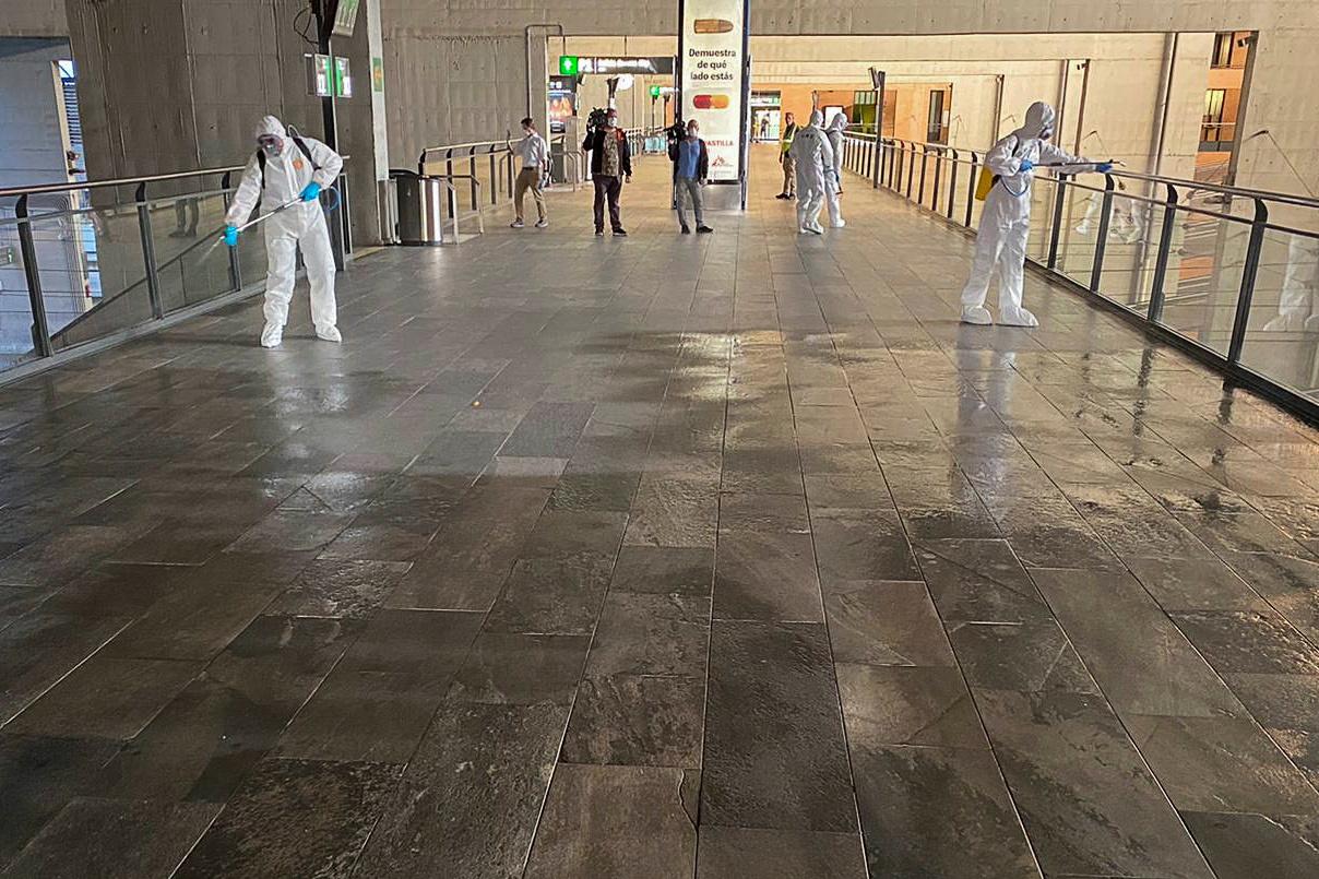 Miembros de la Unidad Militar de Emergencia con trajes de protección, desinfectan los pasillos de la Estación de Santa Justa, en Sevilla. REUTERS/Stringer