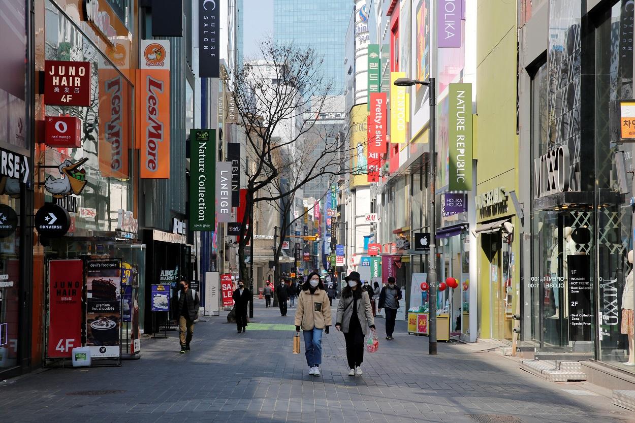 Personas con mascarilla paseando por el distrito comercial de Seúl (Corea del Sur). REUTERS/Heo Ran