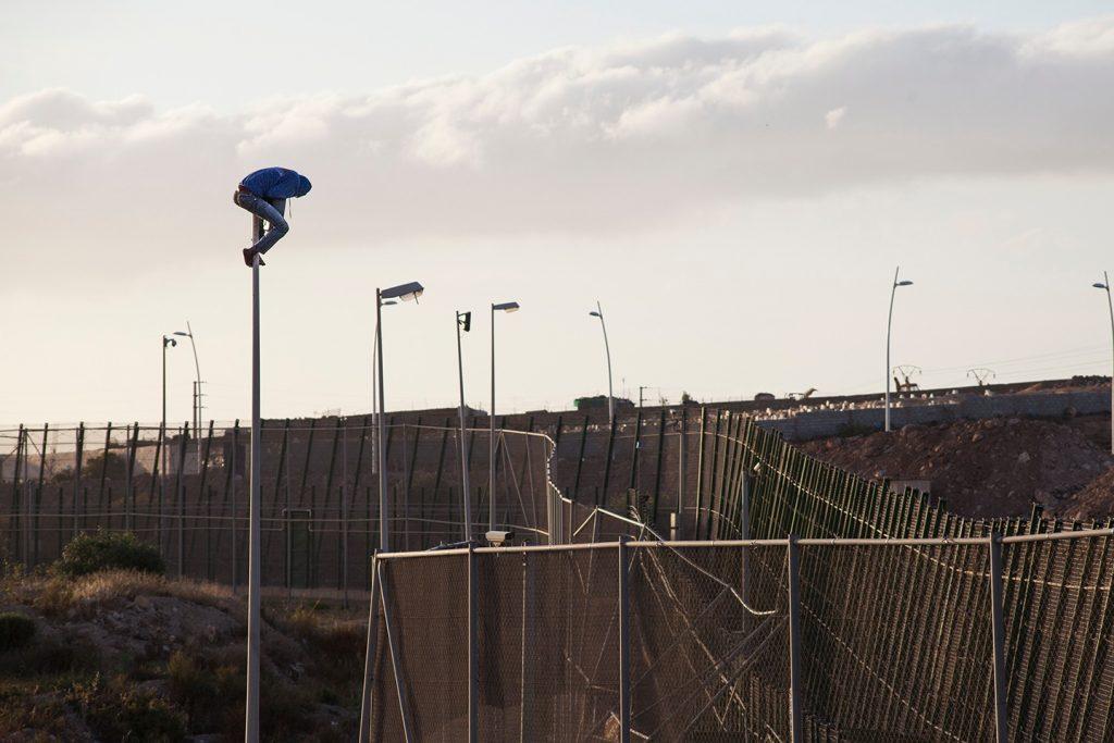 Chico subiéndose a una farola para poder saltar la valla. Foto: Teresa Palomo