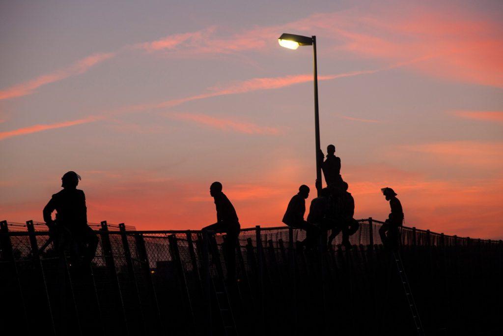 Chicos encaramados en la parte superior de la valla en el atardecer. Foto: Teresa Palomo