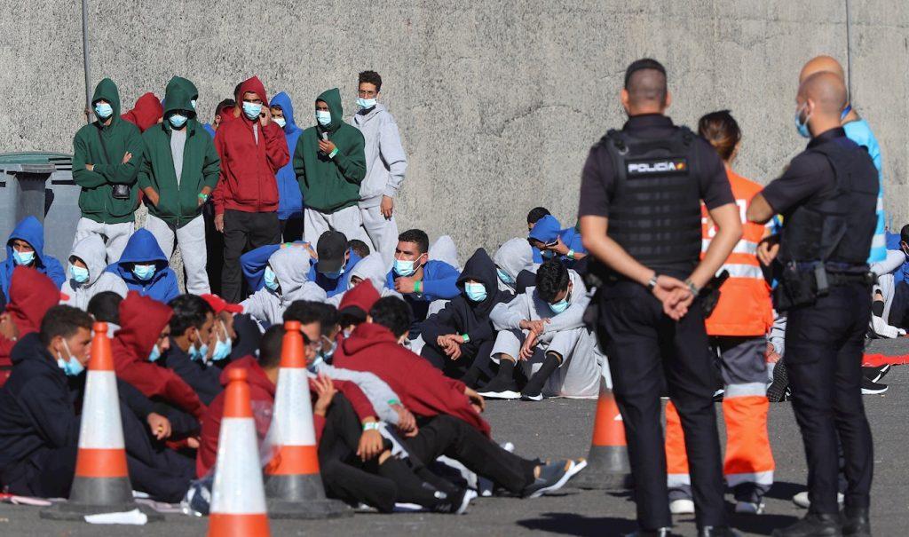 Varios inmigrantes descansan en el muelle de Arguineguín tras ser rescatados por Salvamento Marítimo, el pasado domingo, en Gran Canaria. — Elvira Urquijo A. / EFE