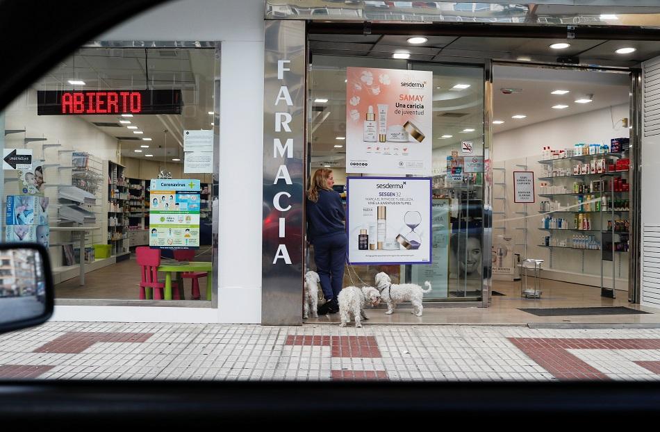 Una mujer espera con sus perros en el exterior de una farmacia en Benidorm. REUTERS/Jon Nazca