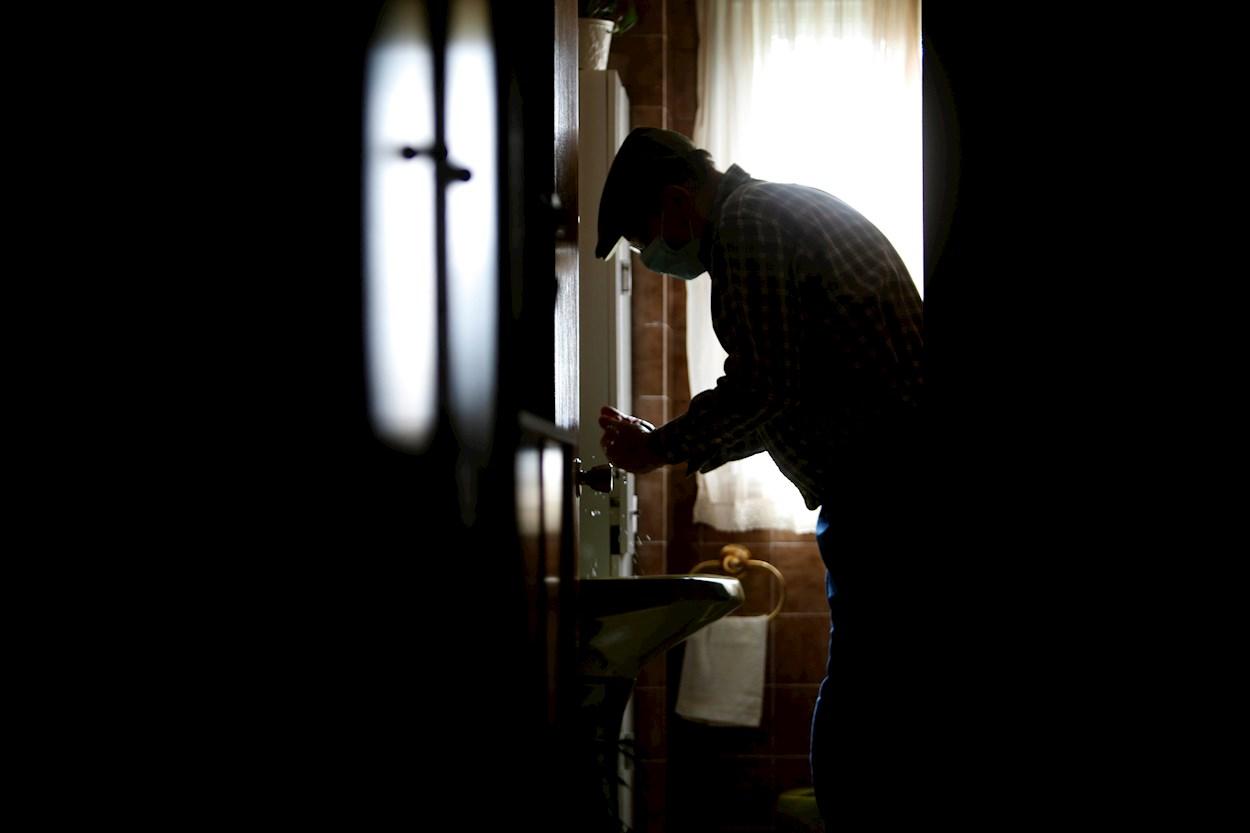 Un hombre se lava las manos en su casa del concello coruñés de Pontedeume, con la mascarilla puesta por recomendación de su médico de cabecera. EFE/Cabalar