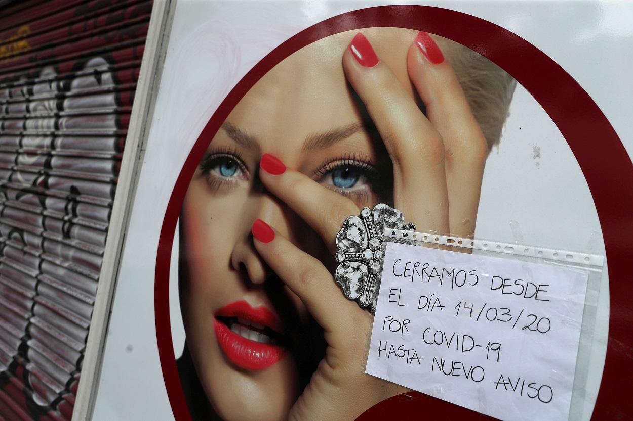 Un letrero en un comercio en Madrid avisa de su cierre hasta que termine la emergencia sanitaria por el coronavirus. REUTERS/Susana Vera