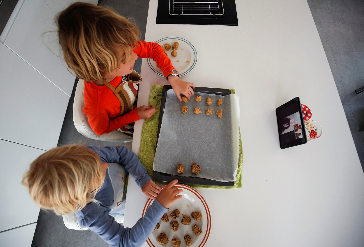 Unos niños preparan unas galletas siguiendo la receta que les dan sus abuelos a través de una 'tablet'. REUTERS/Albert Gea