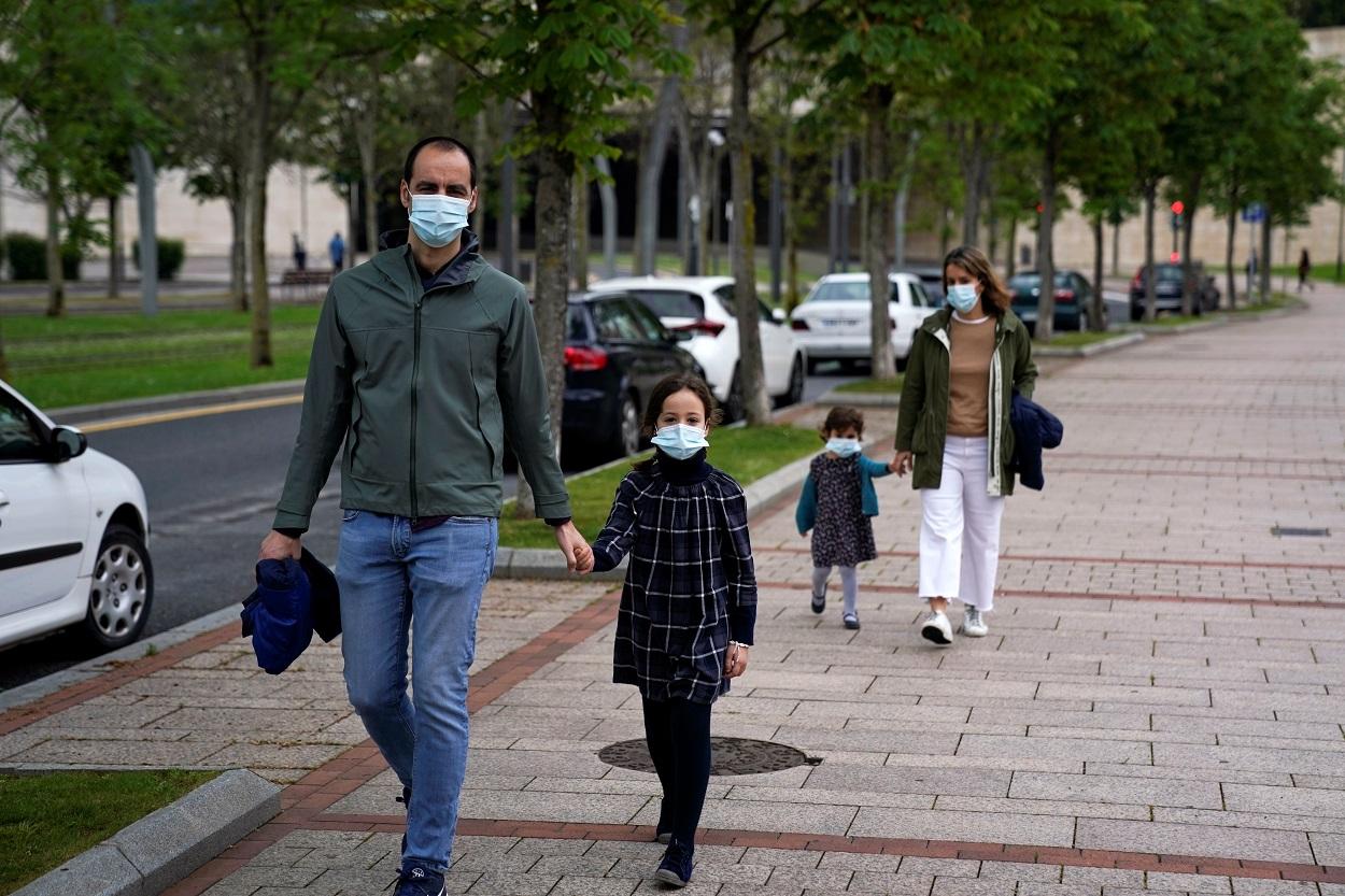 Un matrimonio con sus hijos, todos con mascarilla, dando un paseo en Bilbao. REUTERS/Vincent West