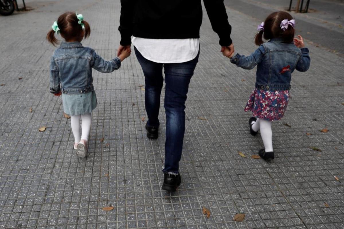 Una madre, con sus hijas, por la calle. EFE