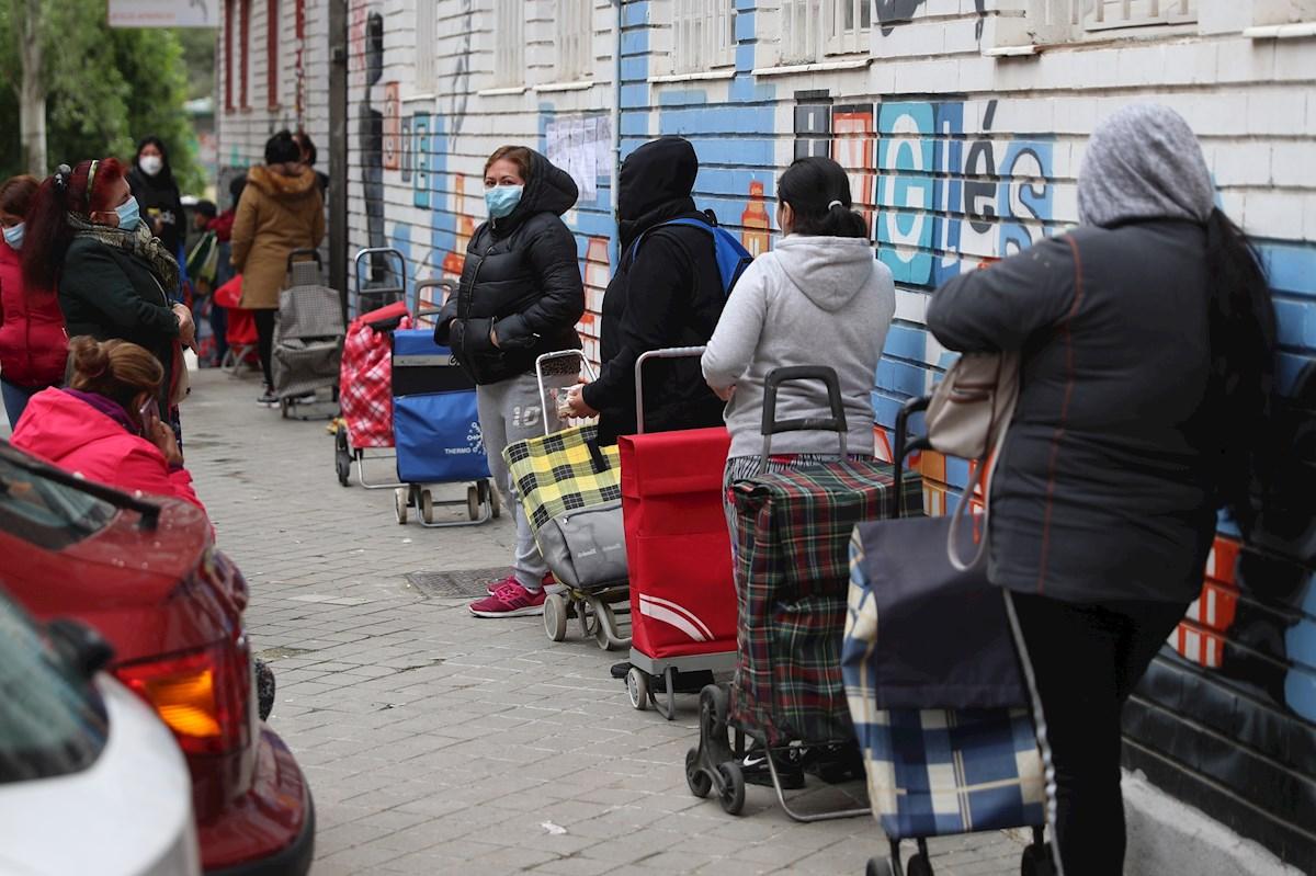 Varias personas esperan en la fila para recoger alimentos proporcionados por la Asociación de vecinos de Aluche. EFE