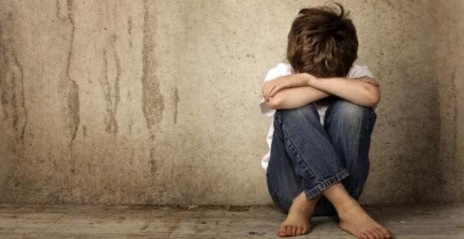 Imagen de archivo de un niño sentado en el suelo tapando su rostro.- EFE