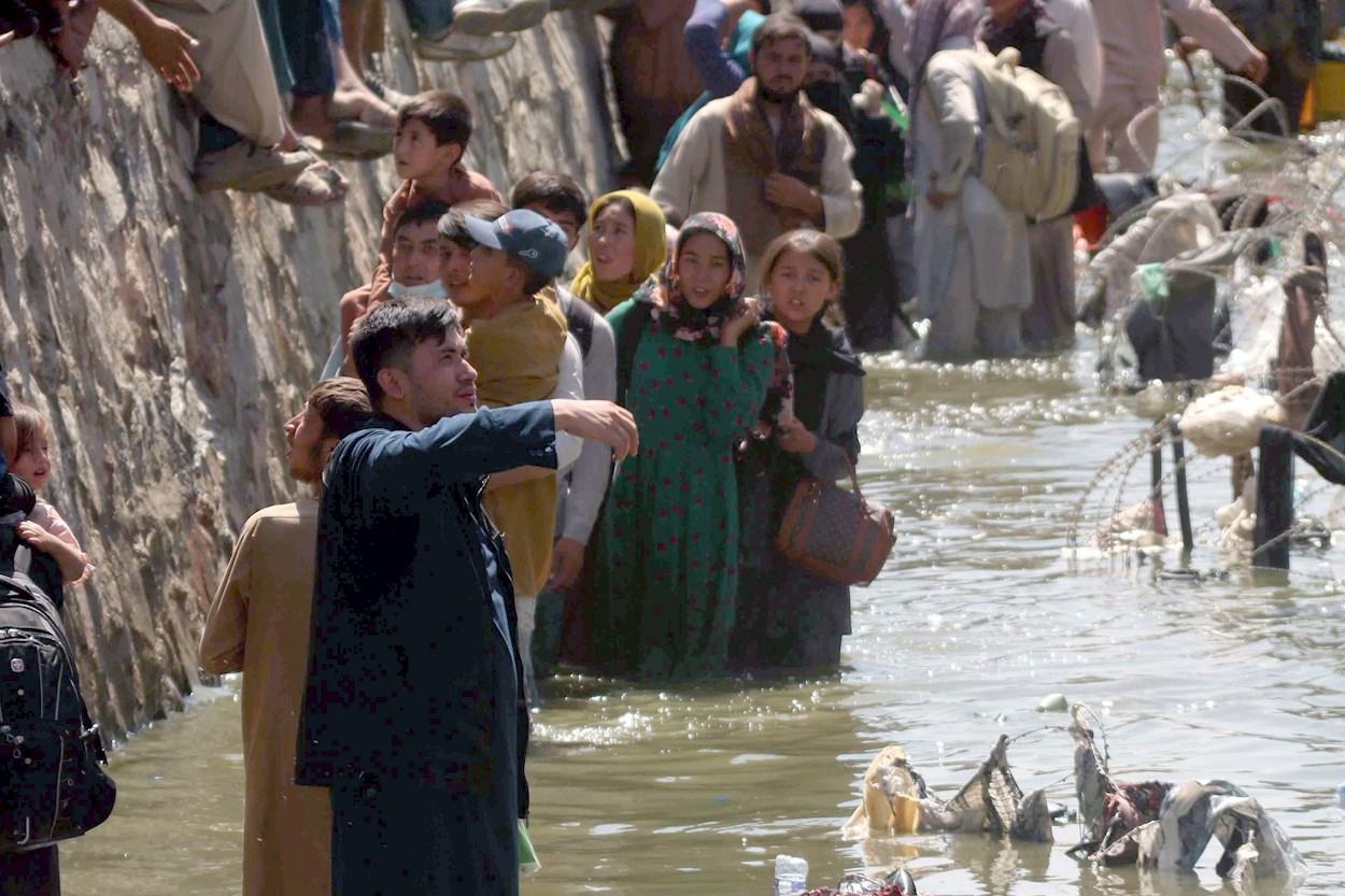 Ciudadanos afganos tratan de llegar hasta las fuerzas militares para mostrar sus credenciales y poder huir del país, junto al aeropuerto internacional de Kabul. EFE/EPA/AKHTER GULFAM