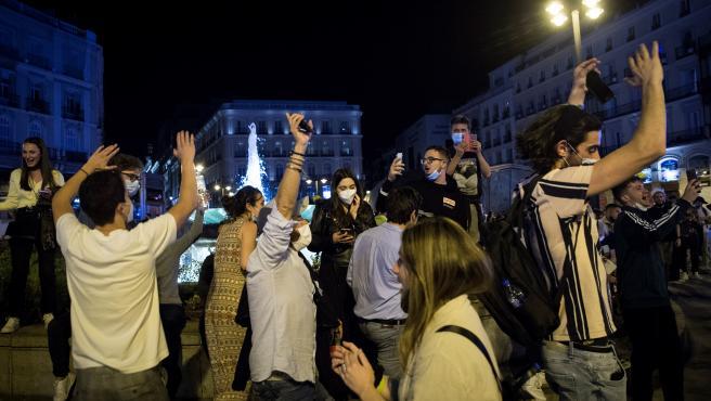 Varios jóvenes saltan y bailan en la Puerta del Sol.EFE