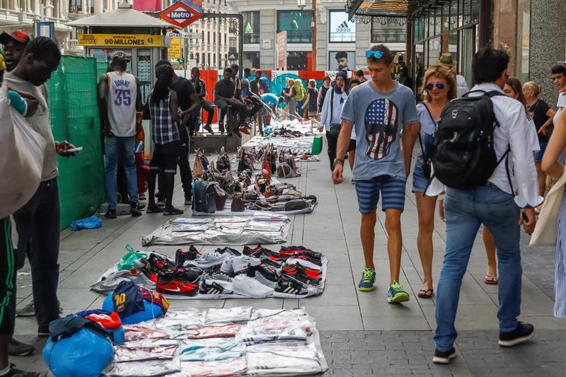 Un grupo de manteros muestra sus productos al público que transita por la Gran Vía de Madrid donde se estan llevando a cabo las obras para la ampliación de sus aceras. EFE/Emilio Naranjo