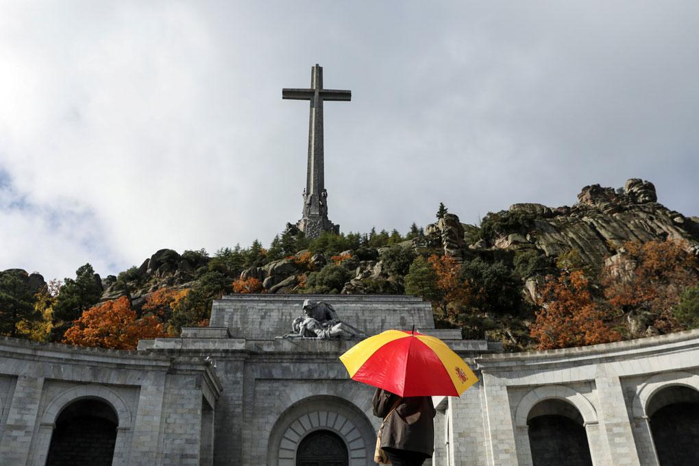 Una mujer con un paraguas con los colores de la bandera española, en el Valle de los Caídos. REUTERS/Susana Vera