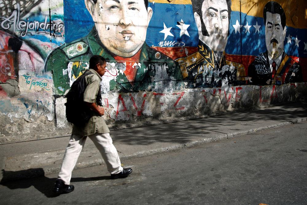 Un hombre camina junto a unos graffitis del héroe revolucionario sudamericano Simón Bolívar, el fallecido presidente de Venezuela, Hugo Chávez y el presidente de Venezuela, Nicolás Maduro, en el barrio José Félix Ribas en Caracas. REUTERS / Carlos Barria
