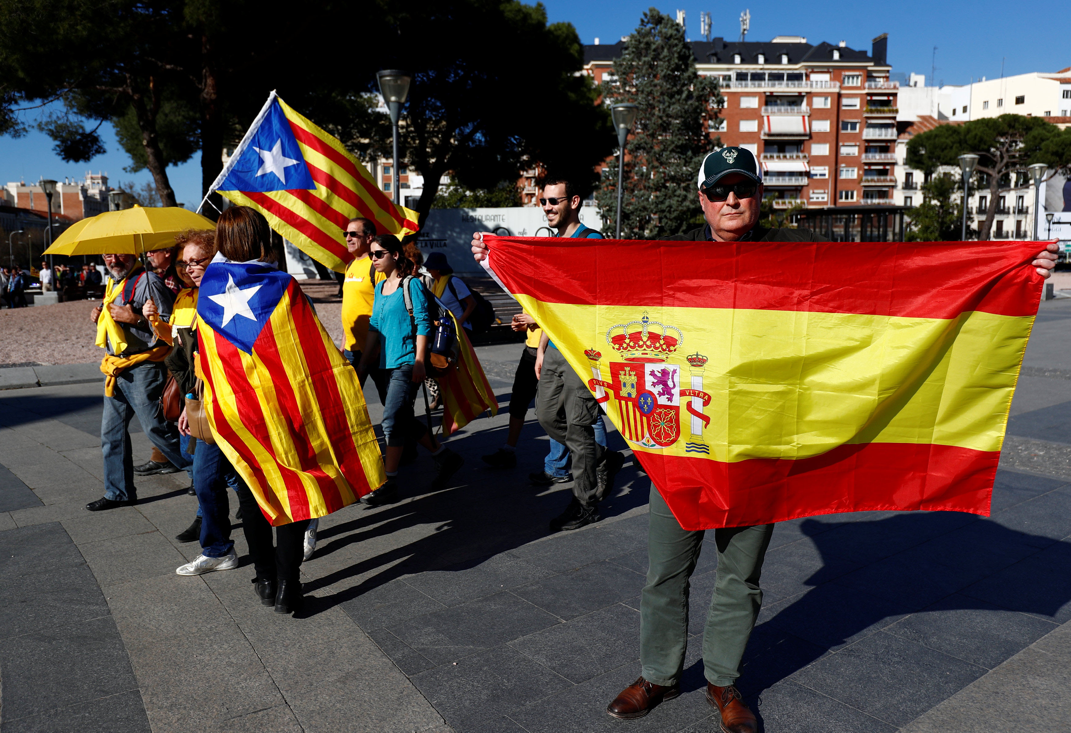 Un hombre sostiene una bandera española junto a personas con banderas estelades, que participaban en la marcha por el derecho a decidir de este fin de semana en Madrid. REUTERS / Juan Medina