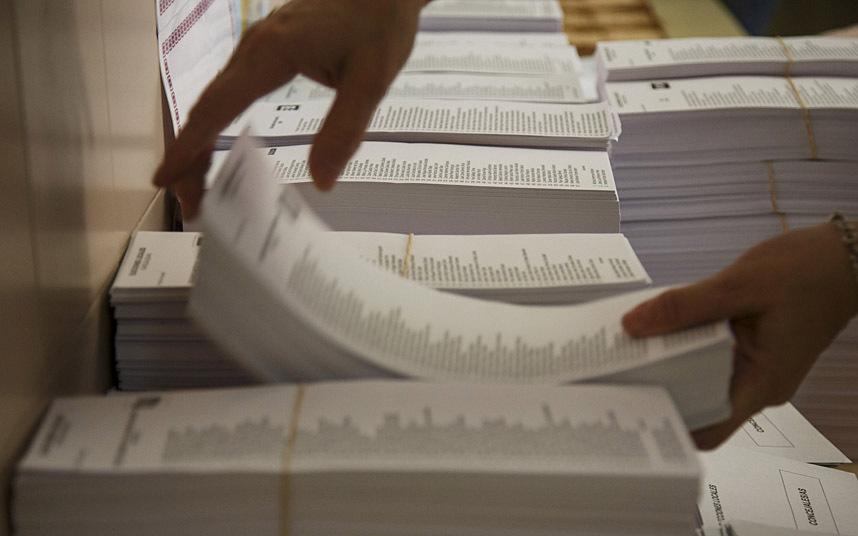 Un funcionario coloca los mazos de papeletas en un colegio electoral en Madrid. REUTERS