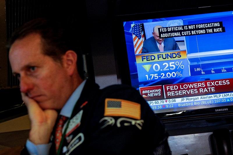 La noticia de la rebaja de los tipos de interés en EEUU en un monitor de televisión en el patio de negociación de la Bolsa de Nueva York.. REUTERS/Brendan McDermid