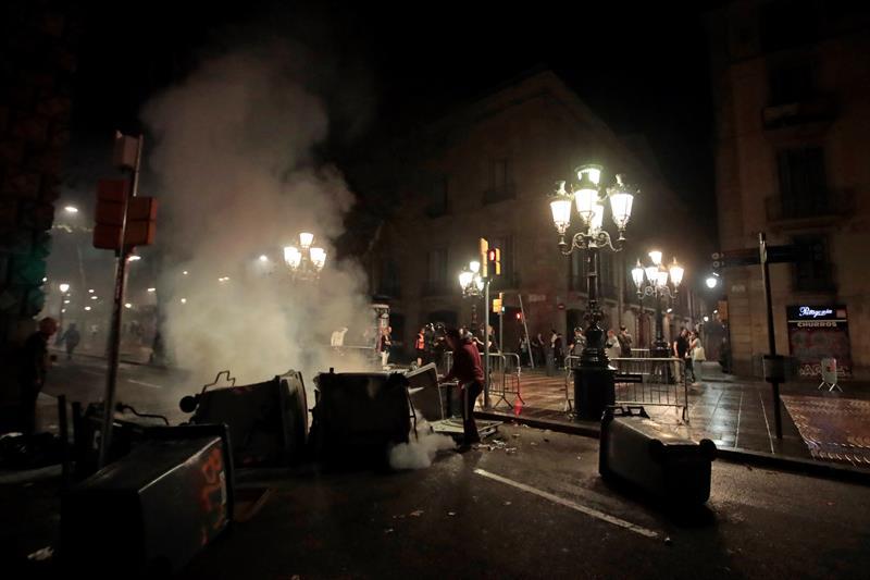 Un vecino apaga un contenedor ardiendo en las Ramblas de Barcelona. EFE/Marta Pérez