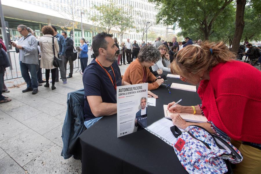 Decenas de ciudadanos esperan frente a la Ciudad de la Justicia, para entregar la documentación de autoinculpación en el marco de una campaña impulsada por la entidad Omnium Cultural. EFE/Marta Pérez