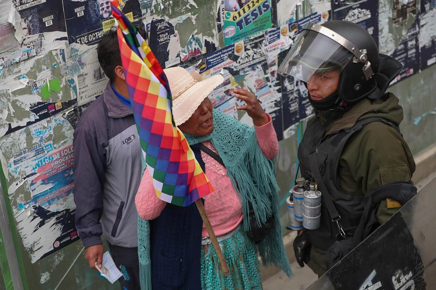 Ciudadanos se enfrentan a los policías antidisturbios durante una jornada de protestas en La Paz, (Bolivia). EFE/Martin Alipaz