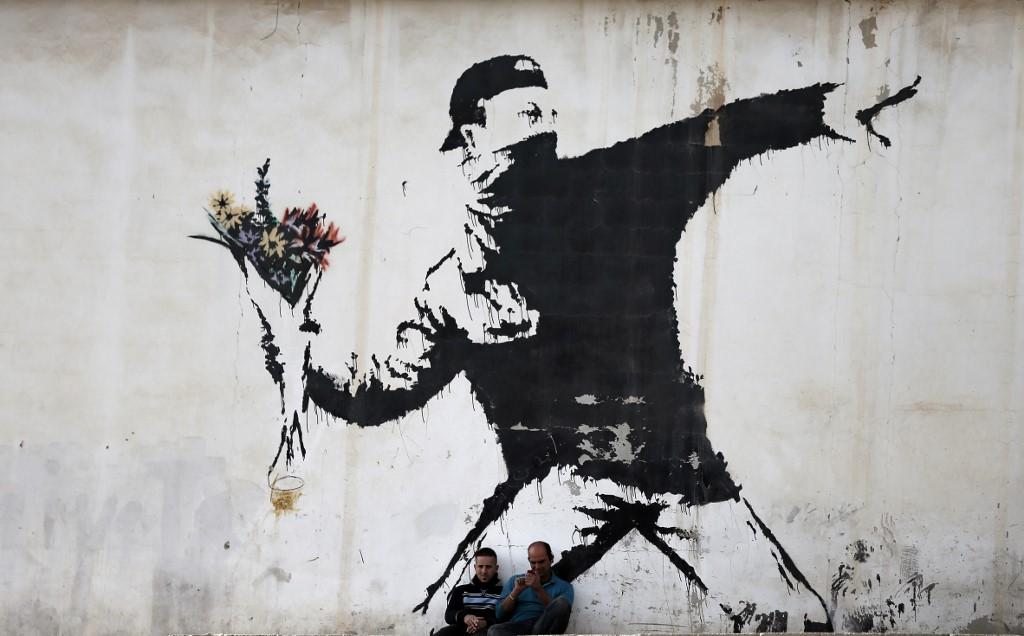 Pintura del artista callejero británico Banksy, en un muro cerca de Belén. AFP/Thomas Coex