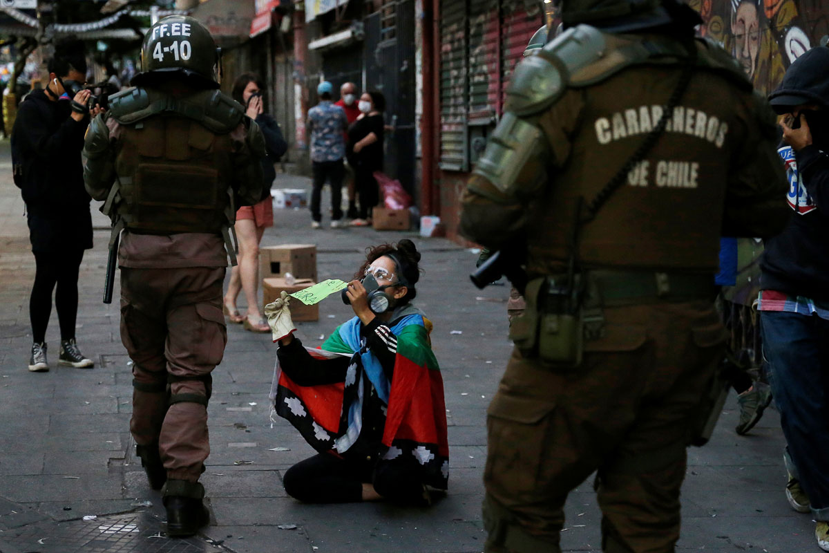 """Una manifestante muestra a los policías un cartel que dice: """"En Chile se tortura"""", durante una protesta contra el gobierno en Valparaíso. REUTERS/Rodrigo Garrido"""