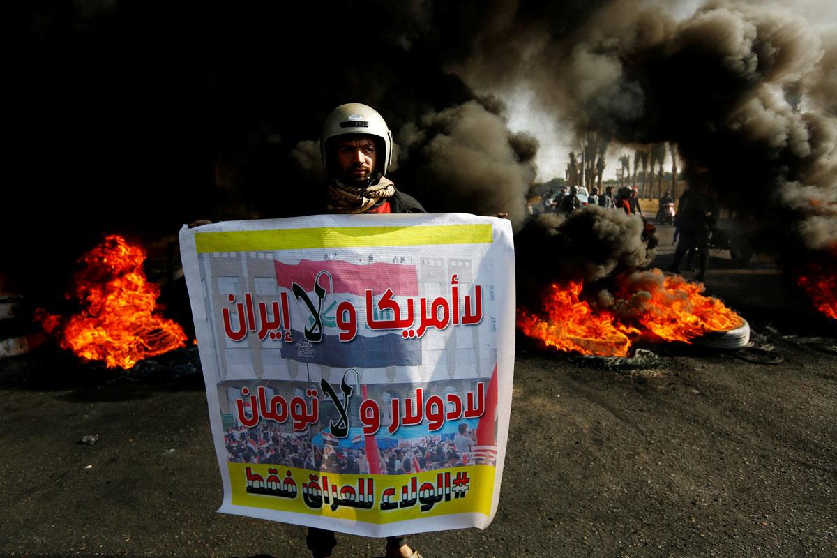 """Un manifestante iraquí lleva un cartel que dice: """"No Estados Unidos ni Irán, No dólar y No Toman, lealtad solo a Irak"""" junto a la quema de neumáticos para bloquear una carretera durante las protestas contra el gobierno en Najaf. REUTERS / Alaa al-Marjani"""