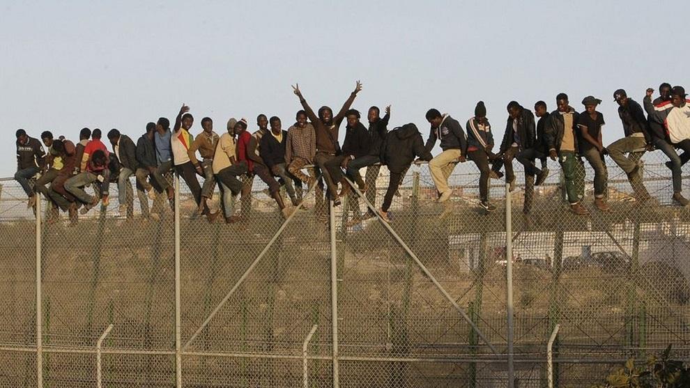 Inmigrantes encaramados a la valla fronteriza de Melilla. EFE