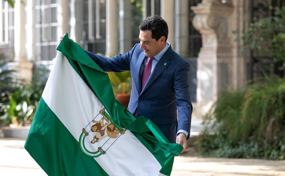 Juan Manuel Moreno con la bandera andaluza en los jardines del Palacio de San Telmo, sede de la Presidencia de la Junta. EFE/Julio Muñoz