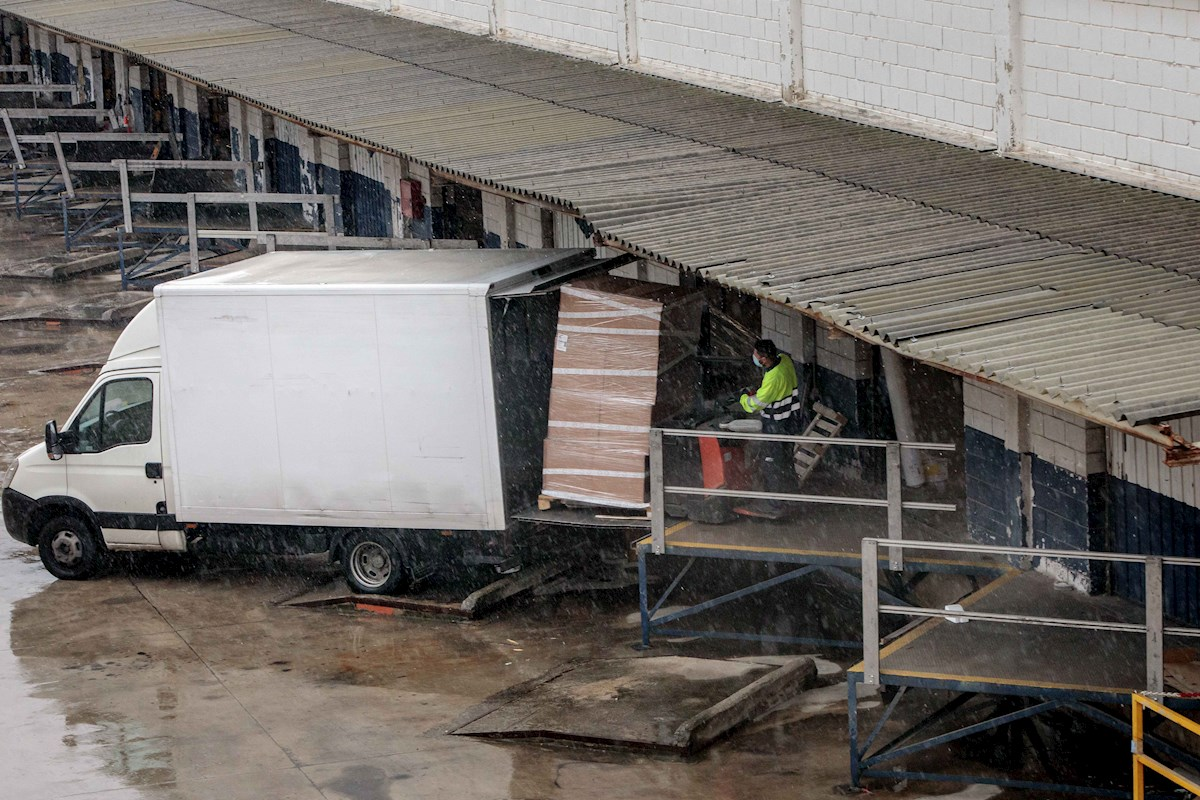 Un transportista carga su camioneta en el polígono industrial Fuente del Jarro, en Paterna (València). EFE/Biel Aliño