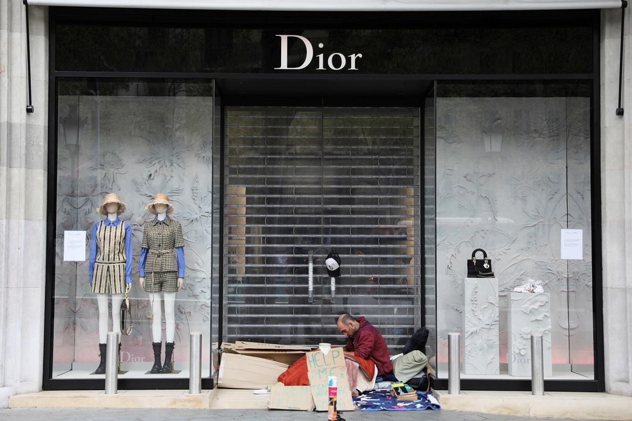Un sin techo, en la puerta de una tienda de lujo en el Paseo de Gracia de Barcelona, durante la crisis del coronavirus. REUTERS/Nacho Doce