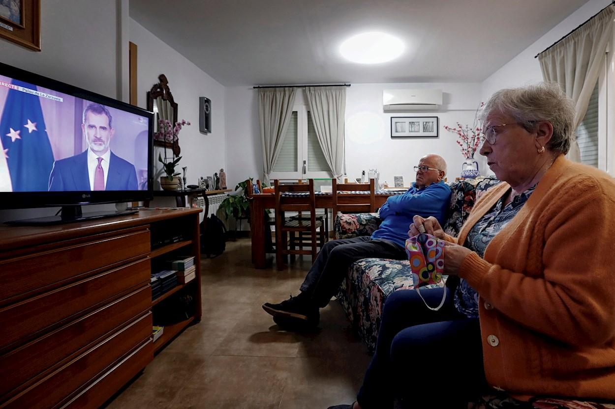 Dos mayores ven, en su domicilio de la localidad barcelonesa de Santa Margarita de Montbuy, el discurso extraordinario del rey Felipe VI, en un mensaje por televisión dirigido a los españoles en relación con la crisis del coronavirus. EFE/Susanna Sáez