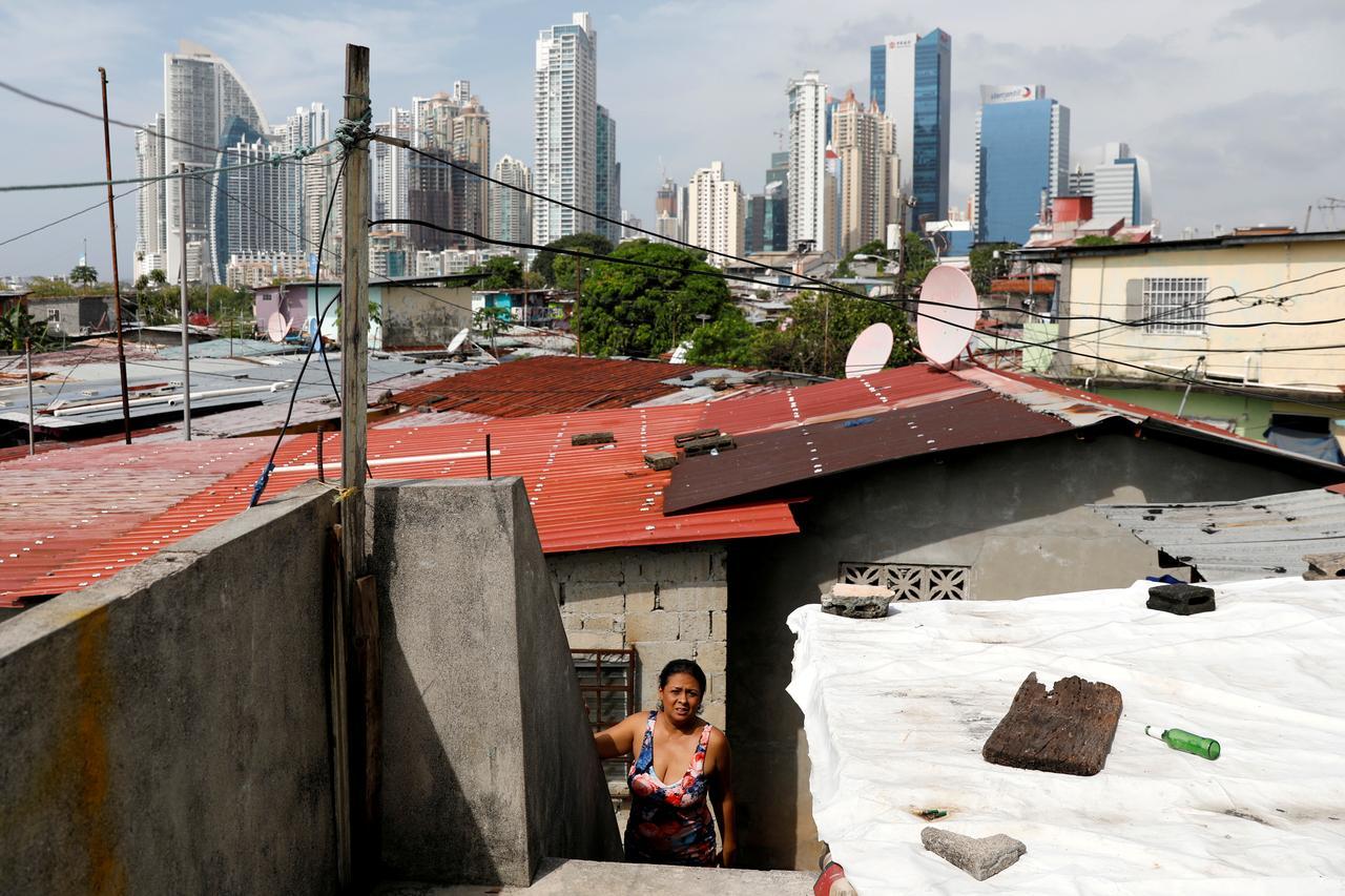 Una mujer sale de su vivienda en una barriada popular en la ciudad de Panamá, con el distrito financiero al fondo. REUTERS/Carlos Jasso