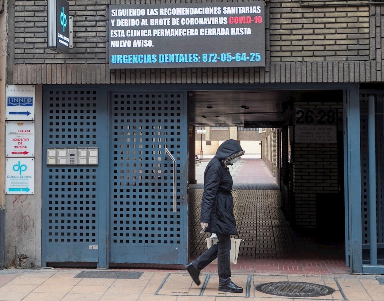 Una mujer camina ante una clínica dental que informa de su cierre debido al coronavirus, en Zaragoza. EFE/ Javier Cebollada