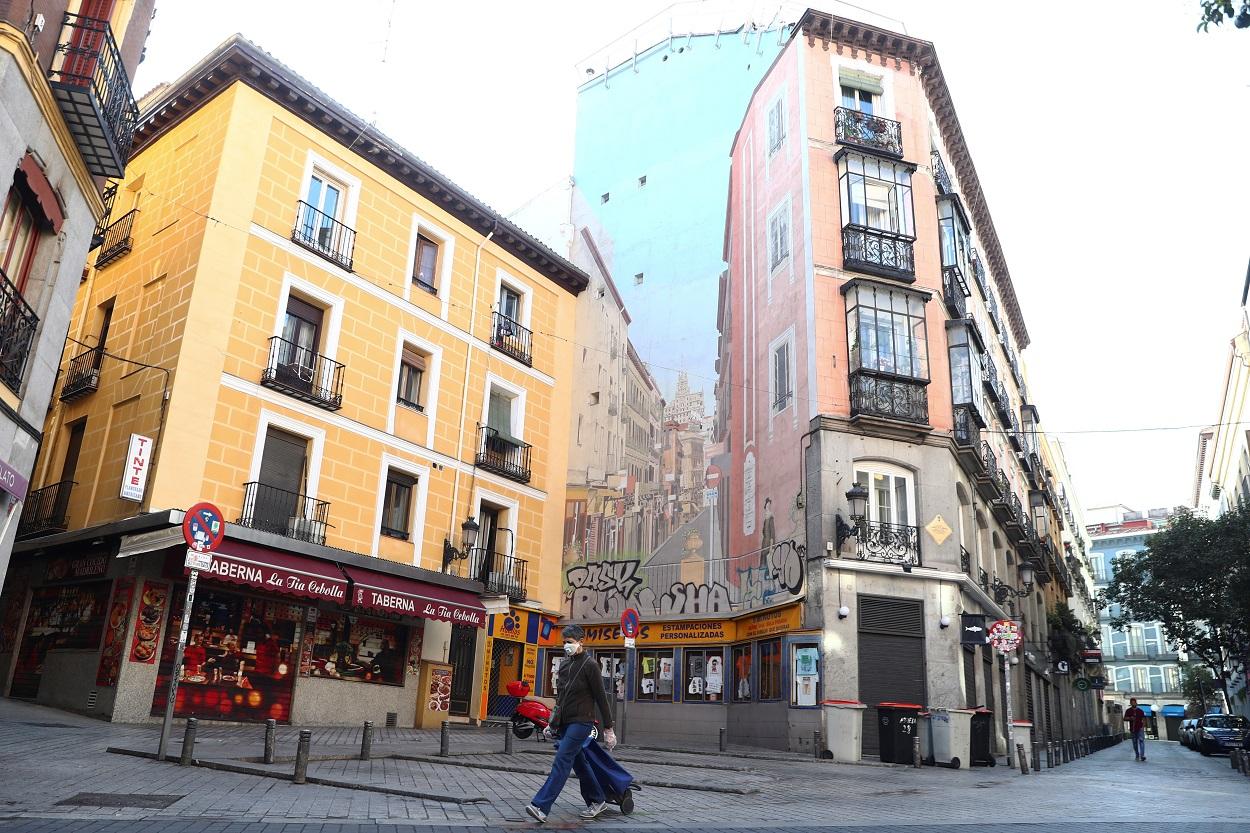 Una mujer con mascarilla y un carrito de la compra, por las calles del centro de Madrid. REUTERS/Sergio Perez