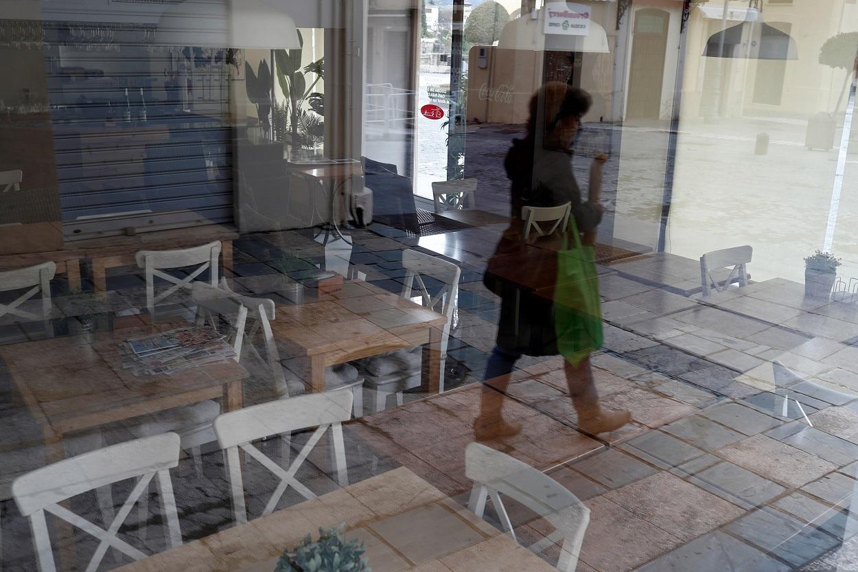 El reflejo de una mujer en el ventanal de un restaurante cerrado, en la localidad malagueña de Ronda. REUTERS/Jon Nazca