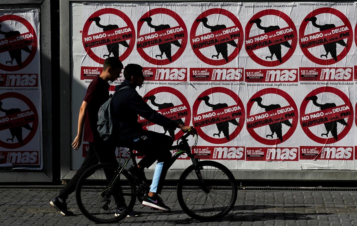 Dos jóvenes pasan junto a un muro empapelado con carteles contra el pago de la deuda, en Buenos Aires (Argentina). REUTERS/Agustin Marcarian