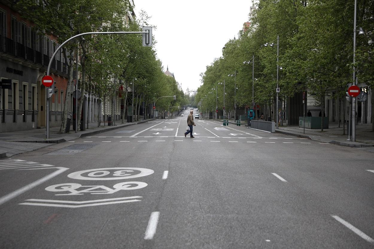 Un hombre cruza la madrileña calle de Serrano, prácticamente desértica, durante el estado de alarma por la pandemia del coronavirus. REUTERS/Sergio Perez