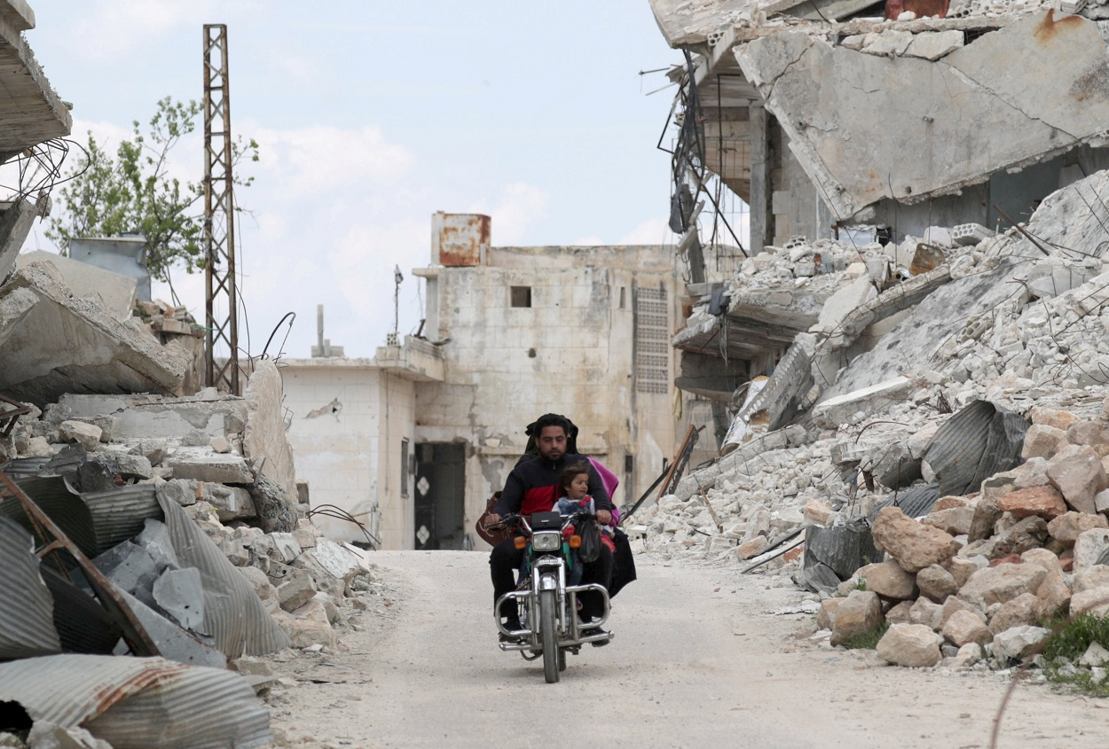 Una familia viaja en una moto cerca de los escombros de los edificios dañados en la región siria de Jabal al-Zawiya. REUTERS / Khalil Ashawi
