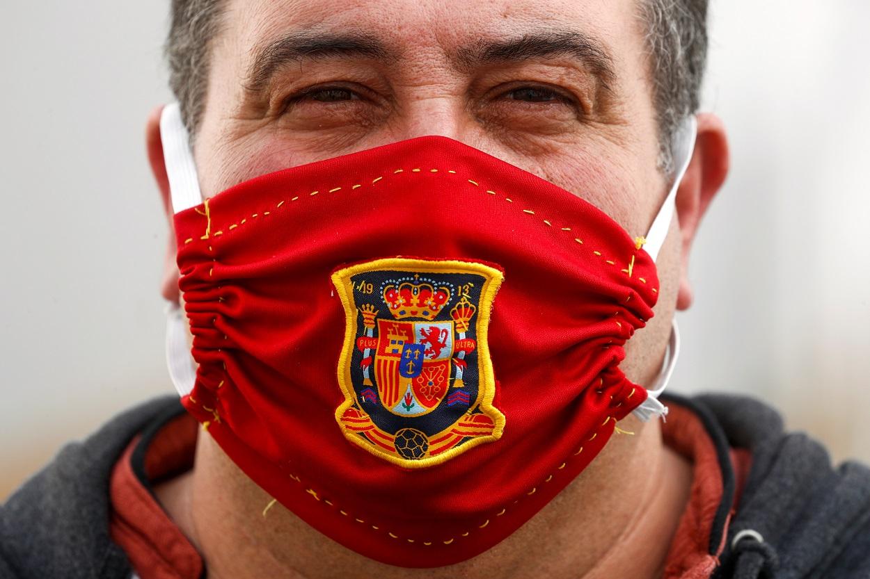 Un hombre, con una mascarilla casera con el escudo de la selección española de fútbol. REUTERS/Jon Nazca