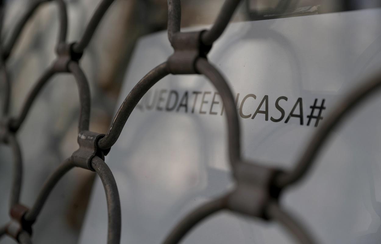 Un letrero con el lema 'Quédate en casa' en el escaparate de un comercio cerrado en Madrid. REUTERS/Susana Vera