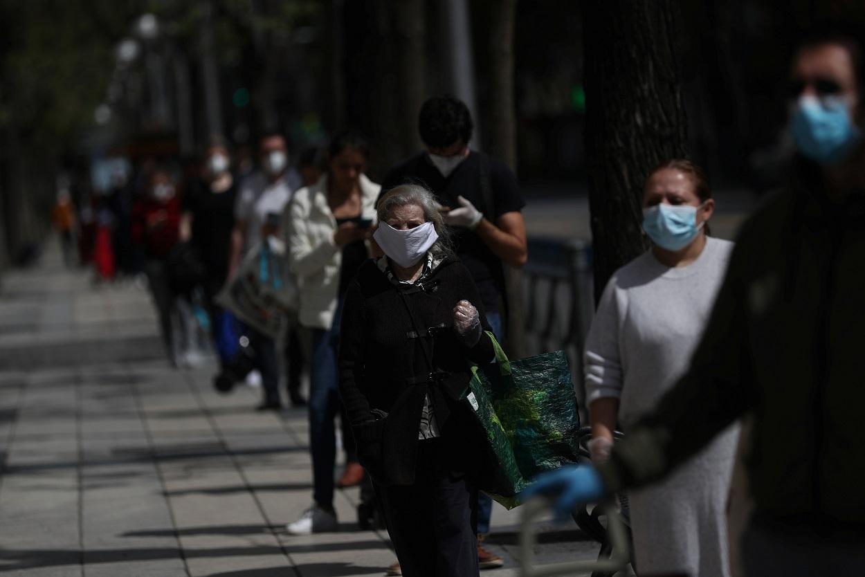 Varias personas con mascarillas guardan cola, manteniendo la distancia social, para entrar en un supermercado en Madrid. REUTERS/Susana Vera