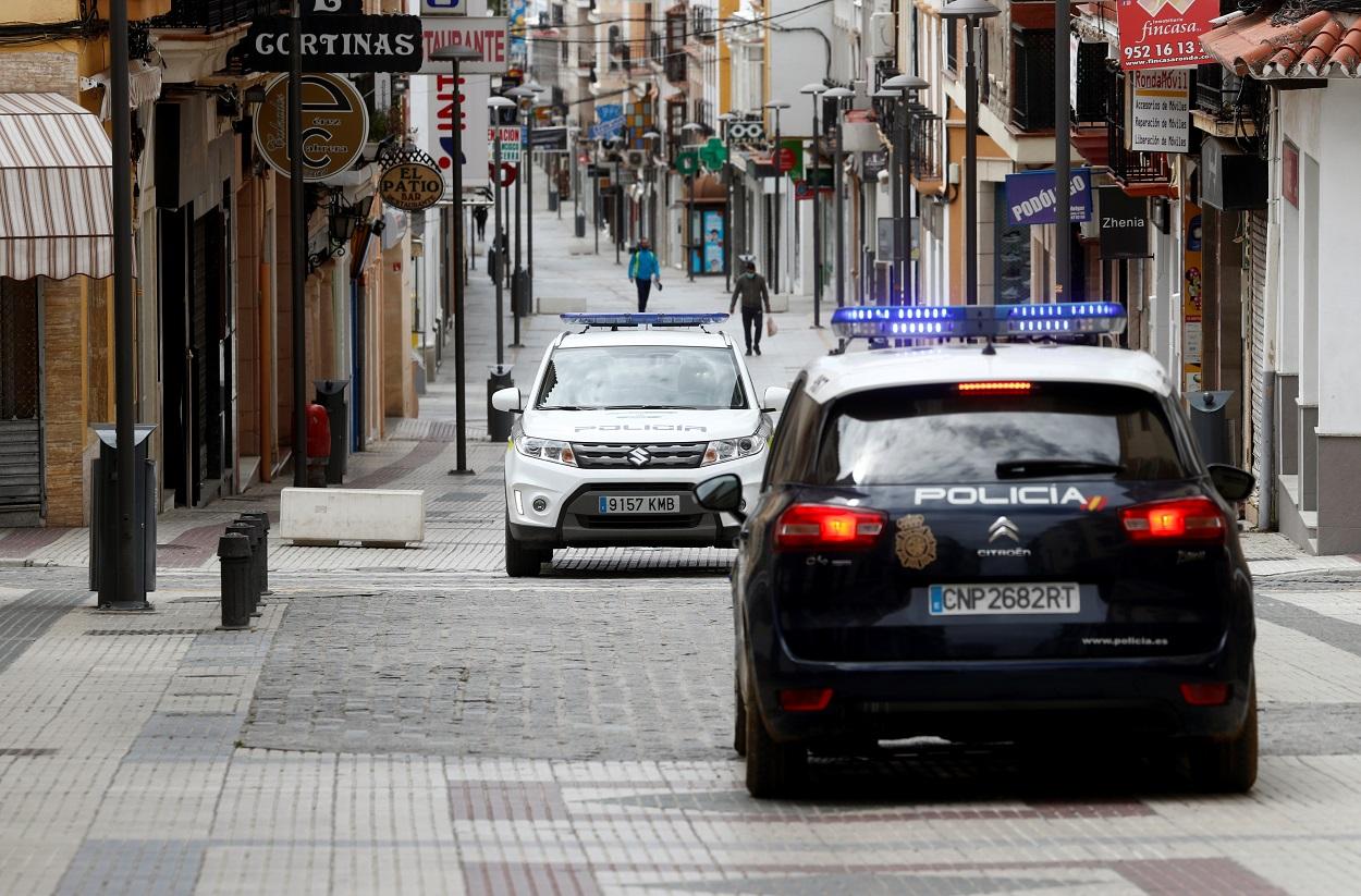 Un coche de la Policía Nacional se cruza con otro de la Policía Local, en una céntrica calle de la localidad malagueña de Ronda, durante el estado de alarma por la pandemia del coronavirus. REUTERS/Jon Nazca