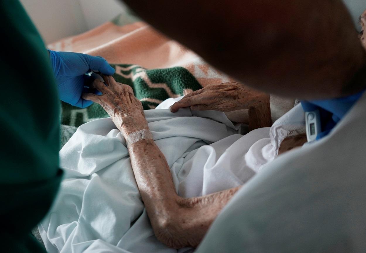 Un sanitario atiende a un anciano en una residencia en la localidad madrileña de Pozuelo de Alarcçon, durante el estado de alarma por la pandemia del coronavirus. REUTERS/Juan Medina