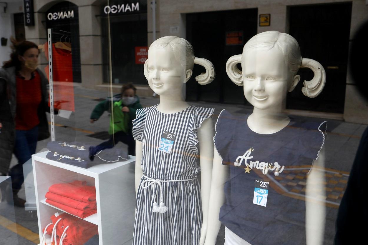 El reflejo de un niño y su madre, ambos con mascarilla, en el escaparate de una tienda de ropa infantil. REUTERS
