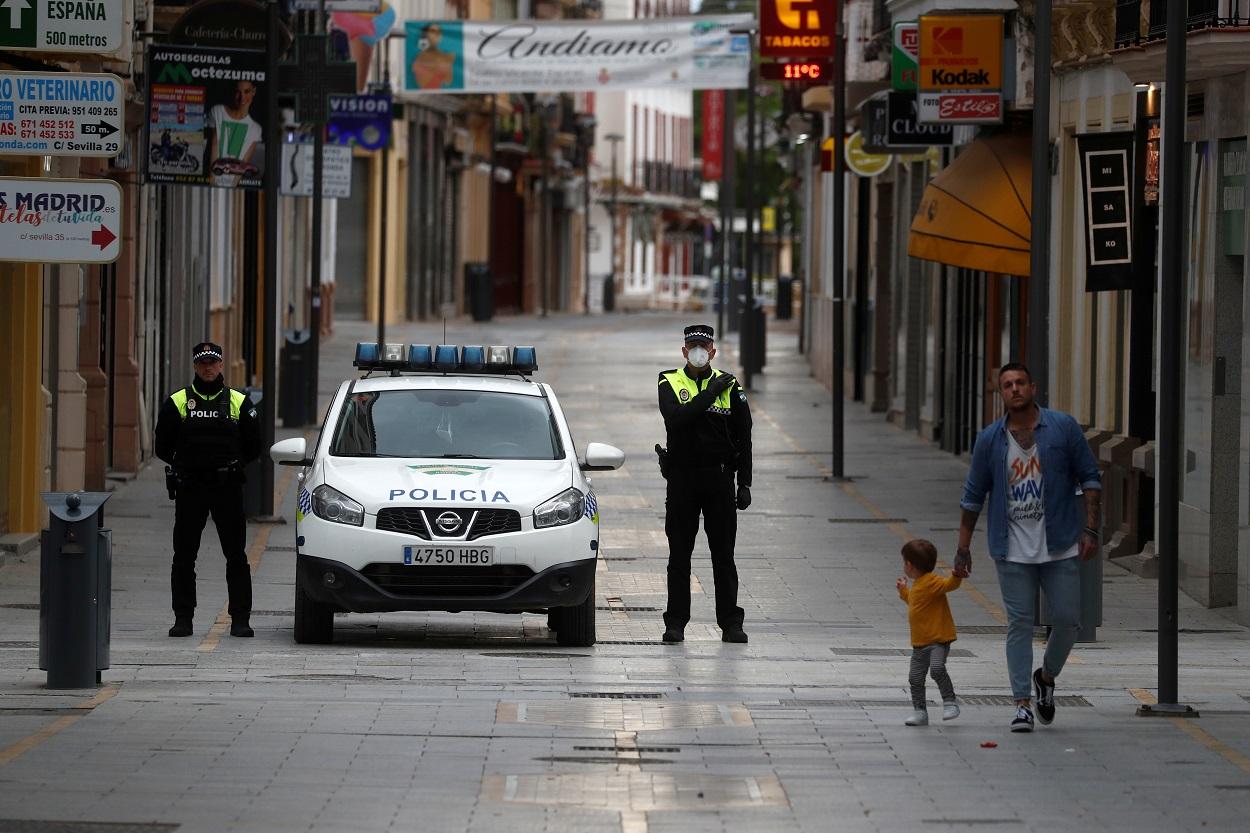 Agentes de la policía local de Ronda (Málaga), junto a uno de sus vehículos, en una de las principales calles de la localidad. REUTERS/Jon Nazca