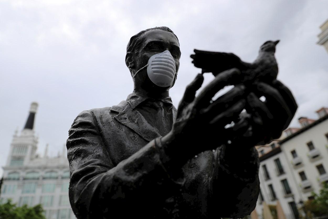 La estatua de Federico García Lorca, en la madrileña plaza de Santa Ana, ataviada con una mascarilla facial durante una nueva jornada de confinamiento por la crisis del coronavirus. EFE/Rodrigo Jiménez